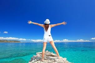 海に向かって大きく手を広げる女性